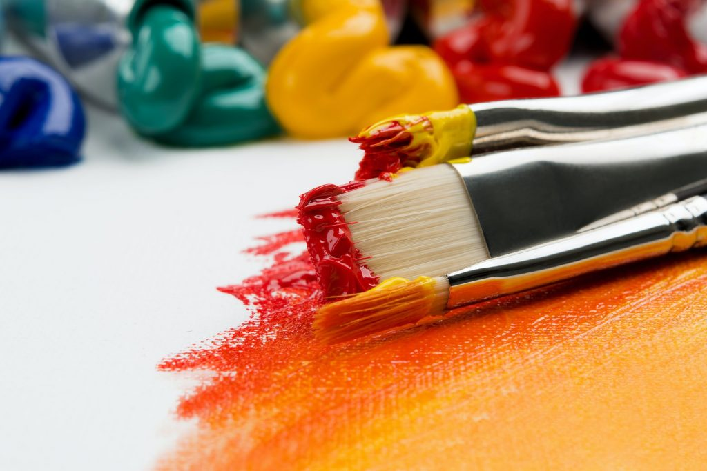 A set of paint brushes with red and orange paint on them