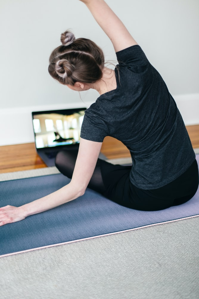 woman on yoga mat doing a virtual fitness lesson